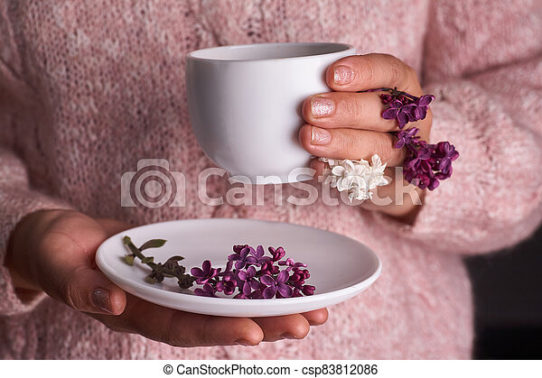 Woman's hand holding a white cup of coffee. With a beautiful lilac flowers. Drink, fashion, morning - csp83812086