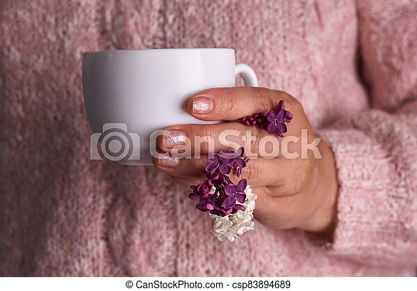 Woman's hand holding a white cup of coffee. With a beautiful lilac flowers. Drink, fashion, morning - csp83894689