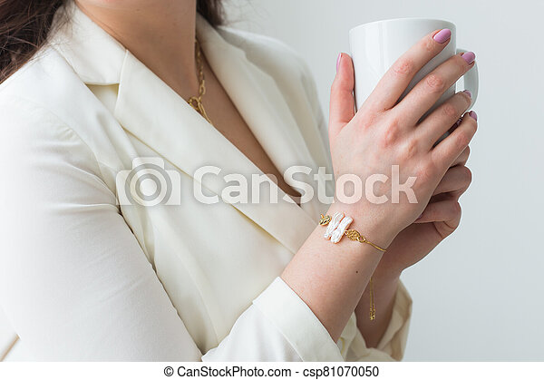 Woman's hand holding a white cup of coffee. With a beautiful manicure close-up. Drink, fashion, morning - csp81070050