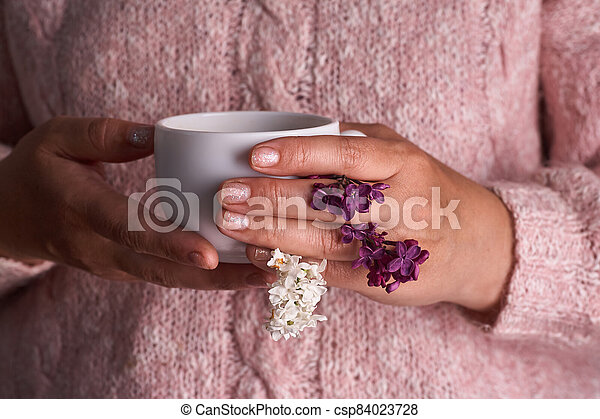 Woman's hand holding a white cup of coffee. With a beautiful lilac flowers. Drink, fashion, morning - csp84023728
