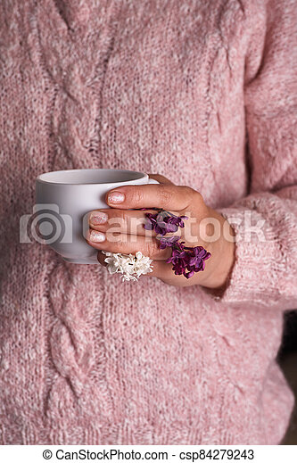 Woman's hand holding a white cup of coffee. With a beautiful lilac flowers. Drink, fashion, morning - csp84279243