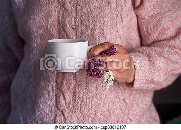 Woman's hand holding a white cup of coffee. With a beautiful lilac flowers. Drink, fashion, morning - csp83812107