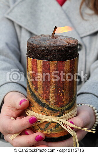 Woman's hands holding lit candle - csp12115716
