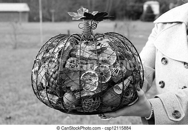 Woman's hands holding metal pumpkin - csp12115884