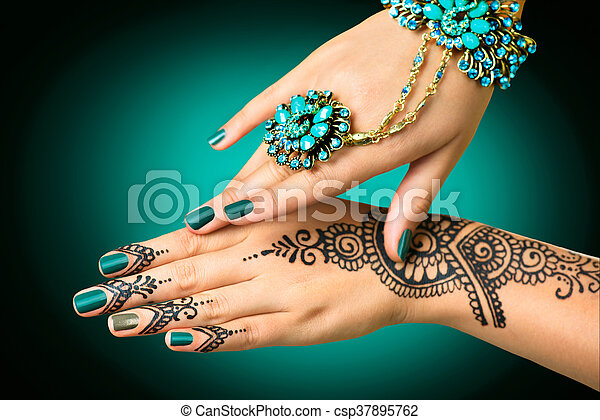 Woman's hands with mehndi tattoo. Hands of Indian bride girl with black henna tattoos - csp37895762