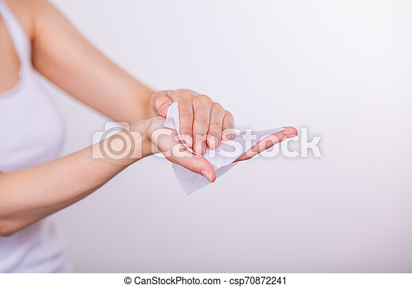 Women carefuly cleaning hands with wet wipes - csp70872241