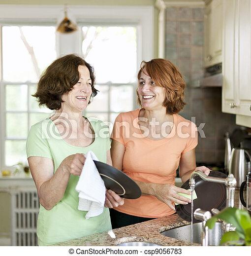 Women doing dishes in kitchen - csp9056783
