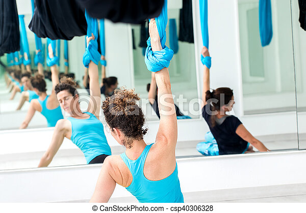 Women exercising bodies at aerial yoga class. - csp40306328