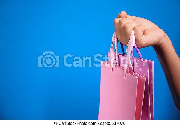 women hand holding shopping bag on blue background, - csp85637076