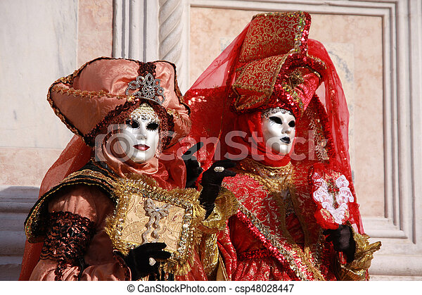 Women in colorful costumes and masks posing at the Venice carnival in  Venice, Italy