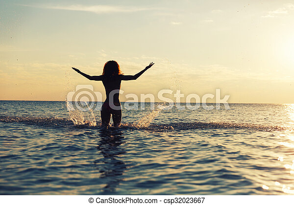 Women in water at sunset - csp32023667