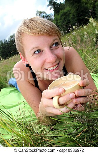 women is drinking from a cup on a meadow - csp10336972