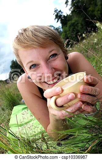 women is drinking from a cup on a meadow - csp10336987