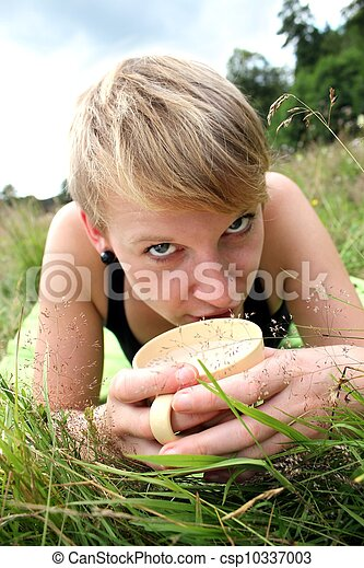 women is drinking from a cup on a meadow - csp10337003