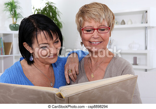 Women looking at a photo album - csp8898294