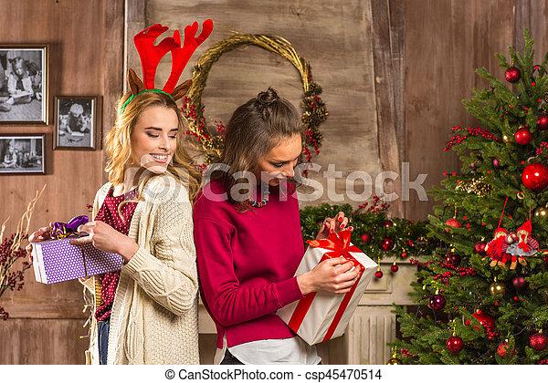 women opening christmas presents csp45470514