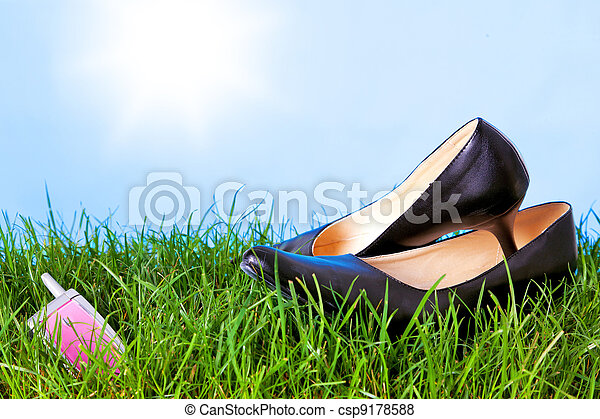Womens high heel shoes and mobile phone on grass - csp9178588