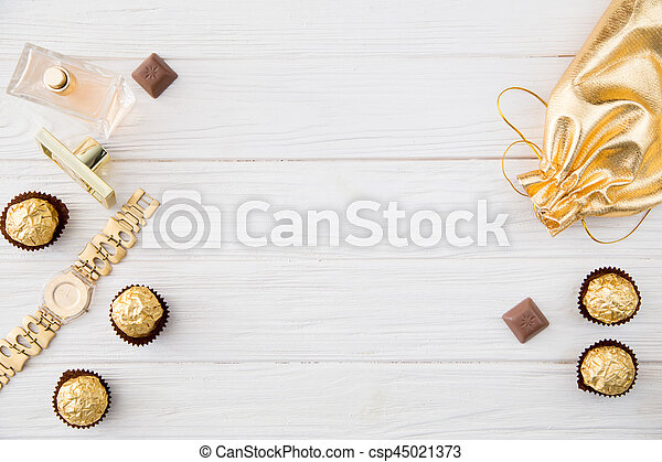 Women's set of accessories and sweets in golden color on wooden background: perfume, candy, chocolate, watch, jewelry, golden bag - csp45021373
