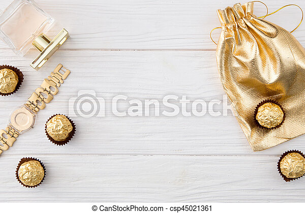 Women's set of accessories and sweets in golden color on wooden background: perfume, candy, chocolate, watch, jewelry, golden bag - csp45021361