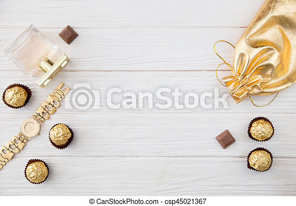 Women's set of accessories and sweets in golden color on wooden background: perfume, candy, chocolate, watch, jewelry, golden bag - csp45021367