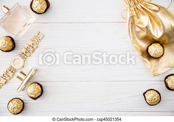Women's set of accessories and sweets in golden color on wooden background: perfume, candy, chocolate, watch, jewelry, golden bag - csp45021354