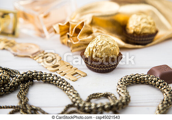 Women's set of accessories and sweets in golden color on wooden background: perfume, candy, chocolate, watch, jewelry, golden bag - csp45021543