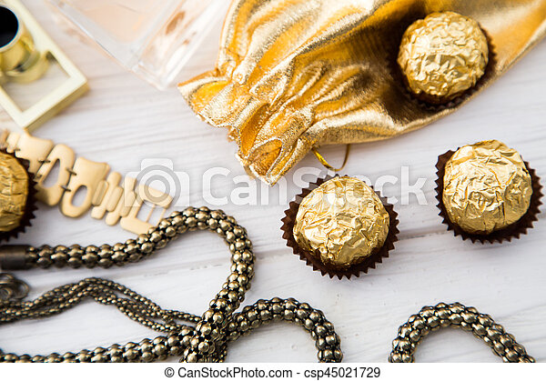 Women's set of accessories and sweets in golden color on wooden background: perfume, candy, chocolate, watch, jewelry, golden bag - csp45021729