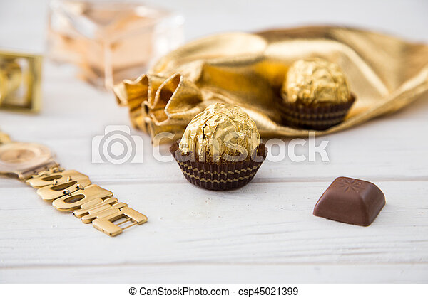 Women's set of accessories and sweets in golden color on wooden background: perfume, candy, chocolate, watch, jewelry, golden bag - csp45021399