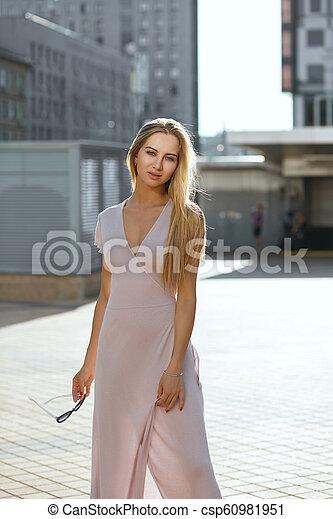 Wonderful blue eyed woman with long hair wearing pink dress posing in sun glare - csp60981951