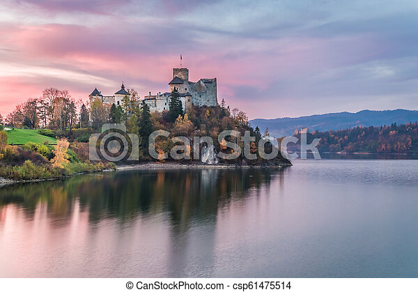 Wonderful castle by the lake at dusk in autumn - csp61475514