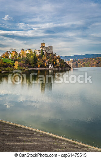 Wonderful castle by the lake at sunset in autumn - csp61475515