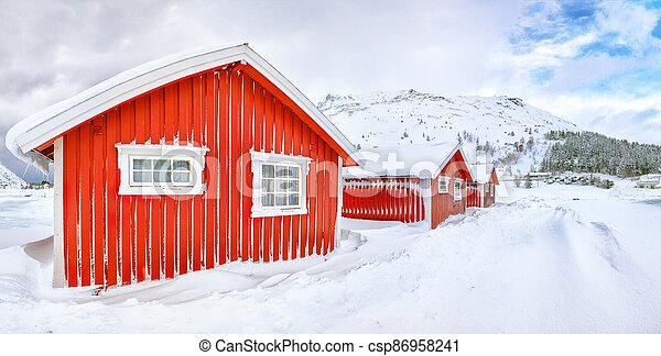 Wonderfull winter scenery with traditional Norwegian red wooden houses on the shore of Rolvsfjord on Vestvagoy island - csp86958241