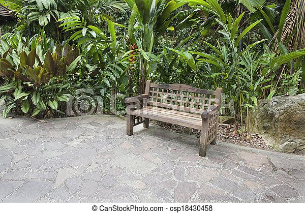 Wood Bench in Tropical Garden - csp18430458