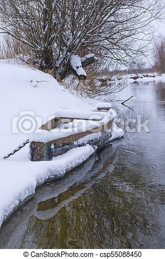 Wood boat covered with snow on shore of winter river - csp55088450