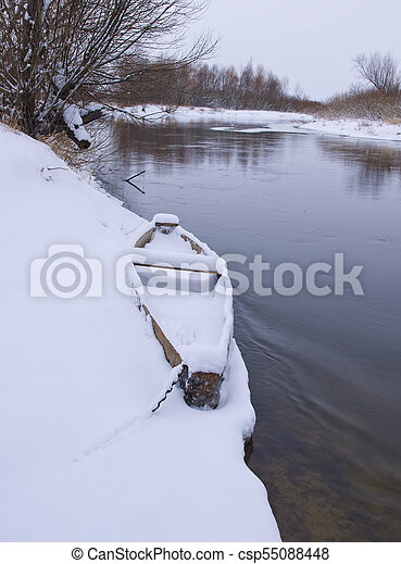 Wood boat covered with snow on shore of winter river - csp55088448