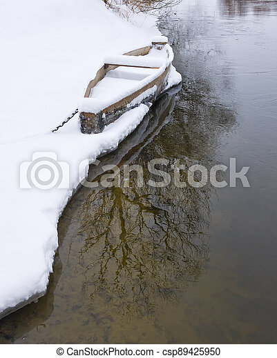 Wood boat covered with snow on the shore of winter river - csp89425950