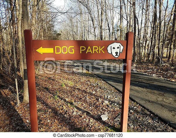 wood dog park sign with yellow arrow and asphalt trail and trees - csp77681120