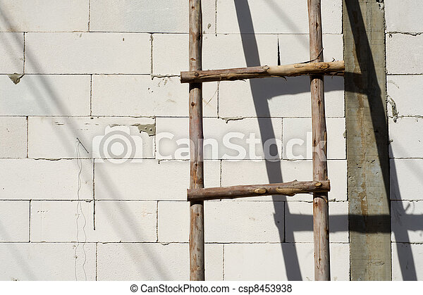 Wood ladder leaning on white brick wall - csp8453938