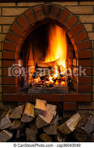 Wood Stack And Logs Burning In Brick Fireplace