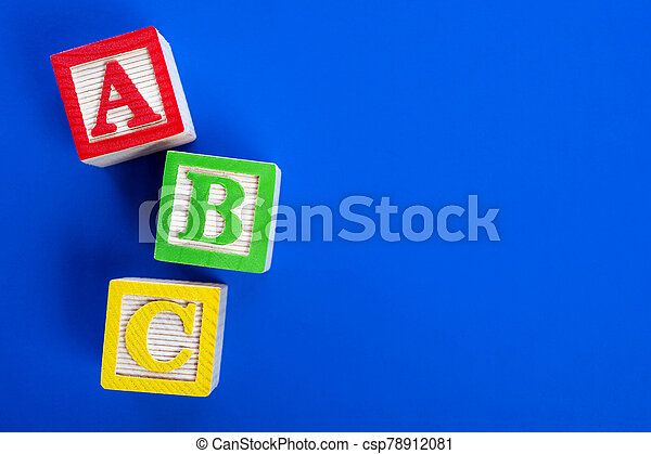 Wooden ABC blocks on blue background - csp78912081