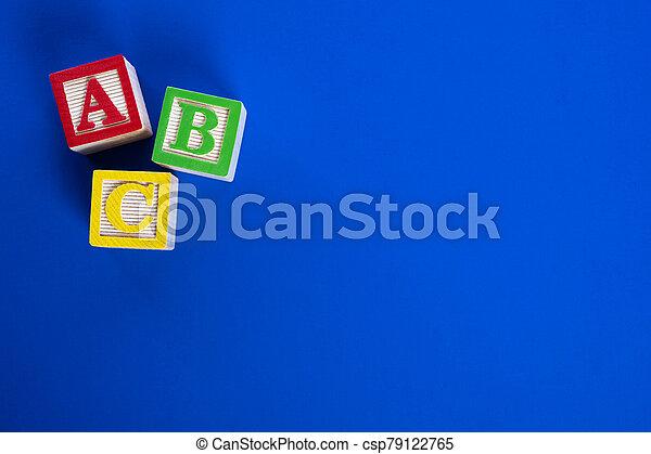 Wooden ABC blocks on blue background - csp79122765