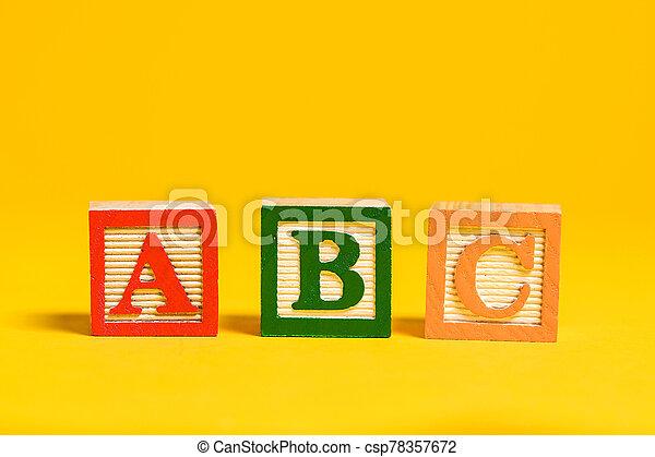 Wooden ABC blocks on yellow background - csp78357672