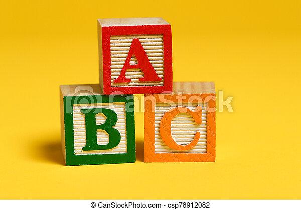 Wooden ABC blocks on yellow background - csp78912082