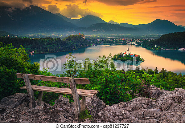 Wooden bench and stunning view with lake Bled at sunrise - csp81237727
