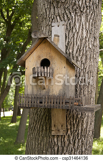 Wooden birdhouse on the tree trunk - csp31464136