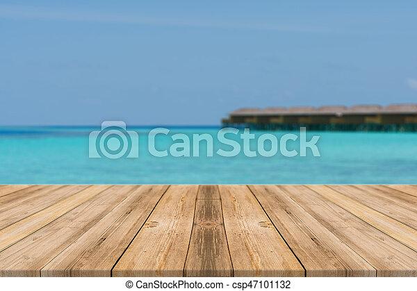 Wooden board empty table top blur sea sky background stock