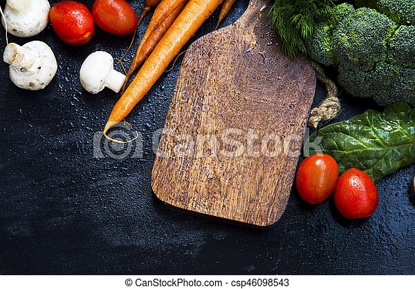 Wooden board with fresh organic vegetables frame, carrots, mushrooms, tomatoes, dill herb, broccoli, spinach leaves - csp46098543