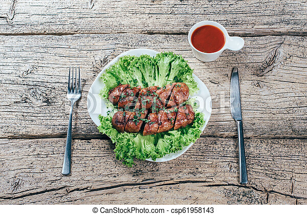 Wooden board with grilled sausages on table - csp61958143