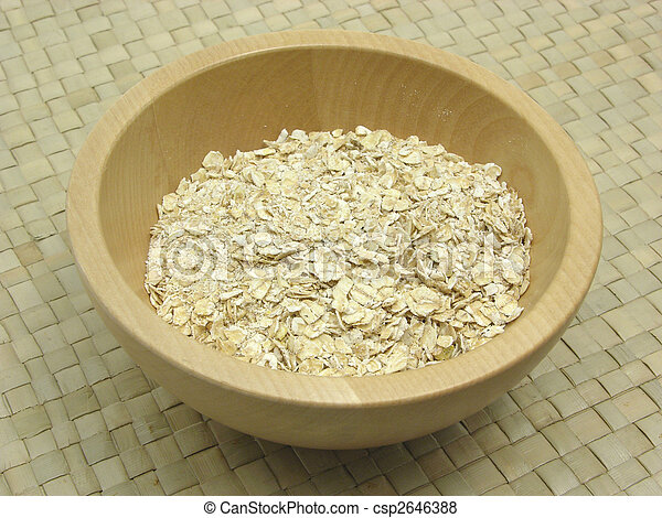 Wooden bowl with oat flakes on rattan underlay - csp2646388
