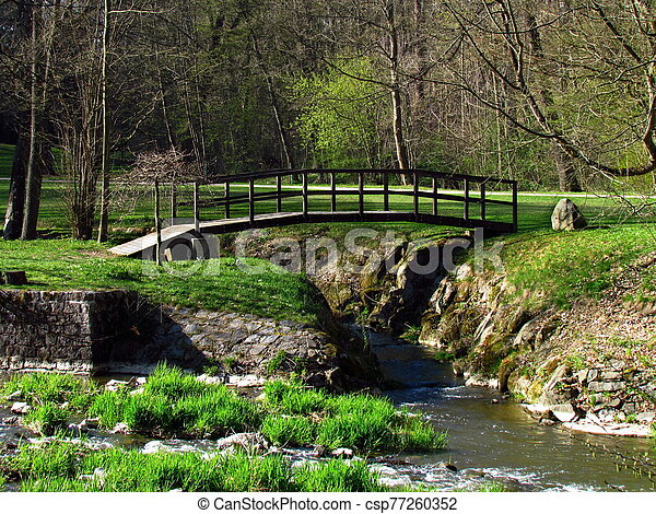 Wooden bridge on river Blanice, public park in city Vlasim, central bohemia region - csp77260352